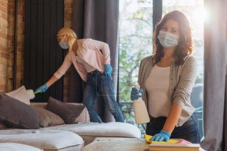 Foto de Enfoque selectivo de la mujer en la mesa de limpieza con máscara médica mientras que el niño usa cepillo de polvo en el hogar. - Imagen libre de derechos