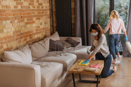 Photo for Mother in medical mask cleaning coffee table while daughter holding dust brush in living room - Royalty Free Image
