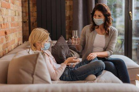 Photo pour Focus sélectif de la mère dans le masque médical tenant un verre d'eau près de la fille avec pot de pilules sur le divan - image libre de droit