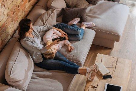 Ansicht der Mutter, die Kanäle anklickt, in der Nähe eines Kindes, das auf der Couch liegt