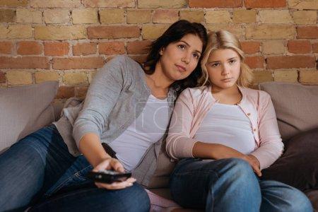 Photo pour Concentration sélective de la mère et de l'enfant regardant la télévision sur le canapé - image libre de droit