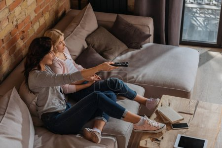 High angle view of smiling woman using remote controller near daughter on couch
