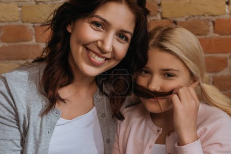 Photo for Smiling mother looking at camera near daughter holding hair near face - Royalty Free Image