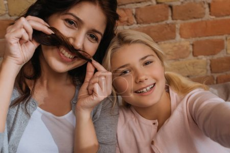 Photo for Cheerful woman and kid looking at camera while holding hair near face - Royalty Free Image