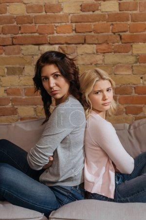 Photo pour Vue latérale de la mère et de la fille regardant la caméra tout en étant assis dos à dos sur le canapé - image libre de droit