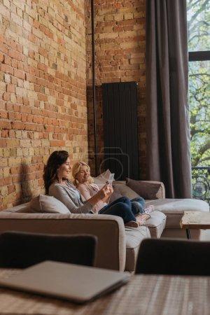 Photo pour Concentration sélective de la mère et de la fille souriantes en utilisant des tablettes numériques sur le canapé - image libre de droit