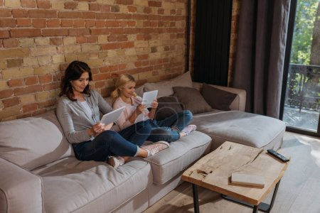 Mother and smiling child using digital tablets on sofa at home