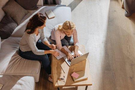 Photo pour Vue aérienne de la mère assise près de sa fille utilisant un ordinateur portable pendant l'apprentissage en ligne à la maison - image libre de droit
