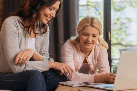 Photo pour Concentration sélective de la mère souriante pointant vers un ordinateur portable près d'un enfant et un ordinateur portable sur la table - image libre de droit