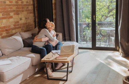 Photo pour Mère souriante étreignant l'enfant près de l'ordinateur portable, ordinateur portable et livre sur la table basse à la maison - image libre de droit