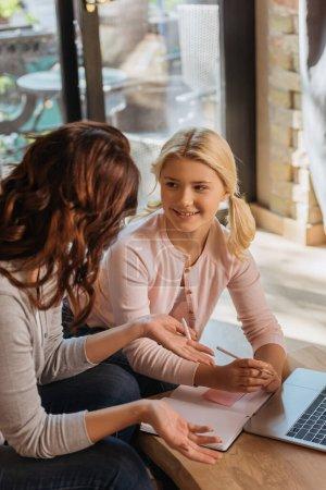 Photo pour Concentration sélective d'un enfant souriant regardant sa mère pointant des mains près d'un ordinateur portable et d'un ordinateur portable sur une table basse - image libre de droit