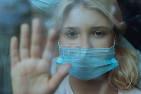 Selective focus of kid in medical mask looking at camera while standing near window
