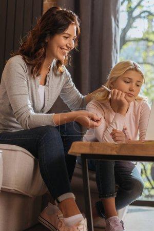 Photo pour Concentration sélective de la mère souriante regardant ordinateur portable près de l'enfant pendant l'éducation en ligne à la maison - image libre de droit