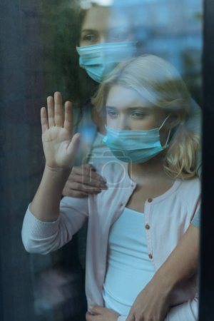 Selective focus of mother in medical mask embracing child near window at home