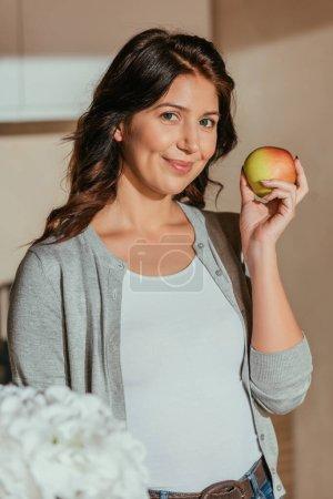 Enfoque selectivo de la hermosa mujer sonriendo a la cámara mientras sostiene manzana orgánica en la cocina