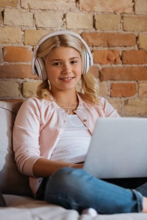 Selective focus of smiling kid in headphone looking at camera near laptop on couch