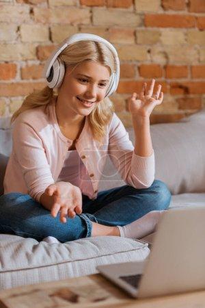 Photo pour Concentration sélective d'un enfant souriant dans un casque ayant un appel vidéo sur un ordinateur portable à la maison - image libre de droit