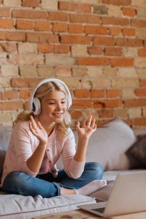 Photo pour Mise au point sélective d'un enfant souriant dans un casque ayant un chat vidéo sur un ordinateur portable à la maison - image libre de droit