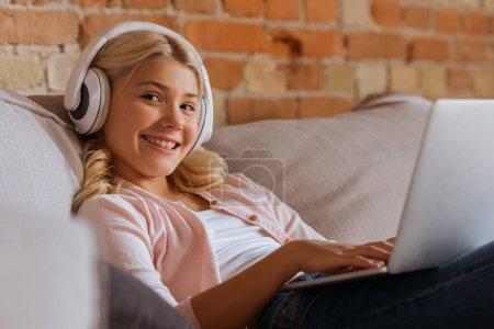Photo pour Concentration sélective d'un enfant souriant dans un casque à l'aide d'un ordinateur portable sur un canapé - image libre de droit
