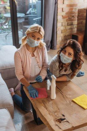 Photo pour Mère et fille dans des masques médicaux regardant la caméra tout en nettoyant la table basse à la maison - image libre de droit