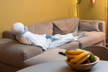 Photo for KYIV, UKRAINE - APRIL 24, 2020: Selective focus of man in hazmat suit and medical mask holding laptop near remote controller and gamepad on couch - Royalty Free Image