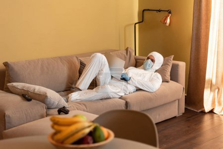 Photo for KYIV, UKRAINE - APRIL 24, 2020: Selective focus of man in hazmat suit and medical mask using laptop near joystick and remote controller on couch - Royalty Free Image