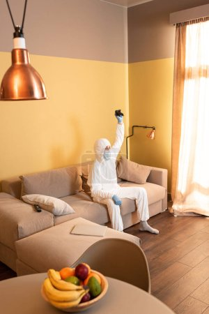 Photo for KYIV, UKRAINE - APRIL 24, 2020: Selective focus of man in hazmat suit and medical mask holding joystick on sofa at home - Royalty Free Image