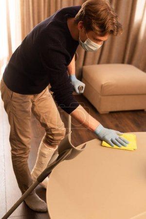 Photo pour Vue latérale de l'homme en masque médical et bandage de plâtre sur la table de nettoyage des jambes dans le salon - image libre de droit