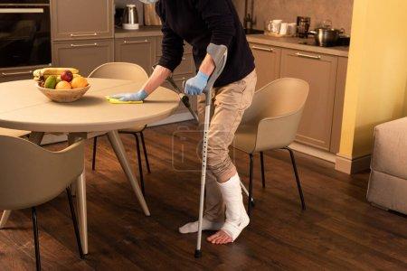 Photo pour Vue recadrée de l'homme en plâtre bandage sur les gants de jambe et de latex table de nettoyage dans la cuisine - image libre de droit