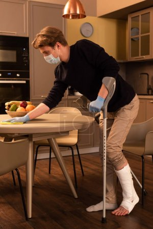 Photo for Side view of man in medical mask with broken leg cleaning table in kitchen - Royalty Free Image