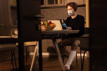 Photo pour Concentration sélective de l'homme dans le masque médical et le bandage de plâtre sur la jambe à l'aide d'un casque et d'un ordinateur portable dans la cuisine - image libre de droit