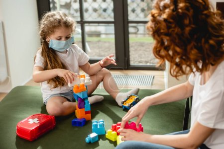 Photo for Selective focus of cute kid in medical mask playing building blocks with redhead mother - Royalty Free Image