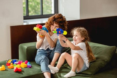 Photo for Curly mother and daughter with water gun playing in living room - Royalty Free Image