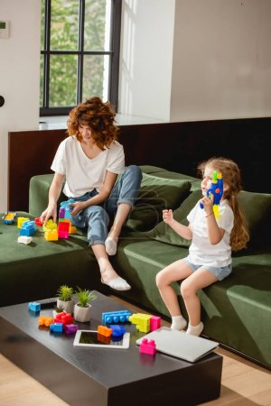 Photo pour Fille mignonne tenant pistolet à eau près de la mère et gadgets dans le salon - image libre de droit