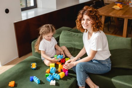 curly mother smiling near daughter playing building blocks in living room