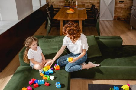 Photo for Redhead mother and cute daughter playing building blocks in living room - Royalty Free Image