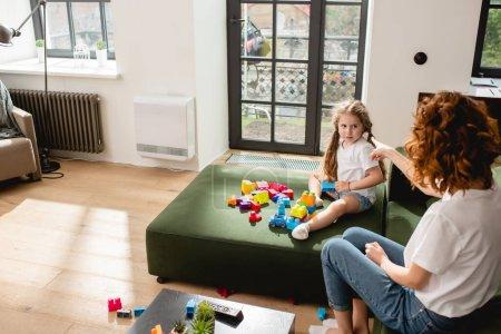 Rückansicht der rothaarigen Mutter, die mit dem Finger auf ihre süße Tochter und Bauklötze auf dem Sofa zeigt