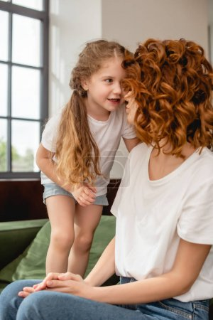 Photo for Cute kid looking at curly mother sitting on sofa - Royalty Free Image