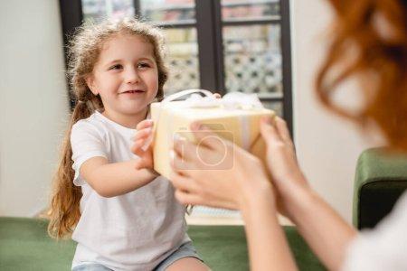 Photo pour Foyer sélectif de fille mignonne donnant cadeau à la mère - image libre de droit