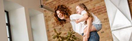 Photo pour Plan panoramique de mère bouclée piggyback fille mignonne - image libre de droit