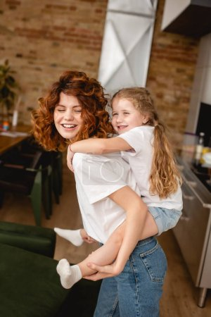 Photo for Positive and curly mother piggybacking cute daughter - Royalty Free Image