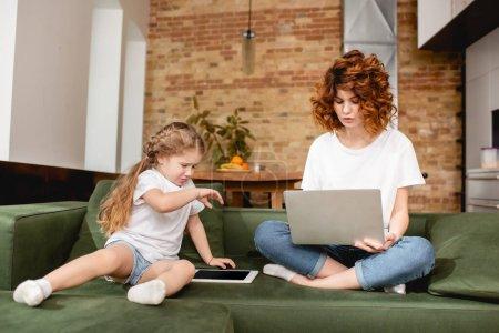 Photo pour Pigiste rousse en utilisant un ordinateur portable près de fille bouleversée avec tablette numérique - image libre de droit