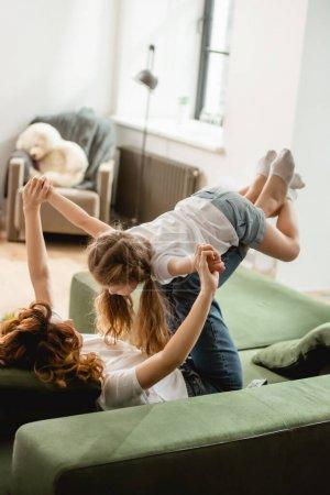 Photo pour La mère couchée sur un canapé, levant sa fille et tenant la main dans le salon - image libre de droit
