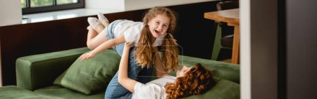 panoramic orientation of curly mother lying on sofa, lifting happy daughter and holding hands in living room