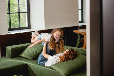 Photo pour Foyer sélectif de la mère bouclée couchée sur le canapé, soulevant fille heureuse et tenant la main dans le salon - image libre de droit
