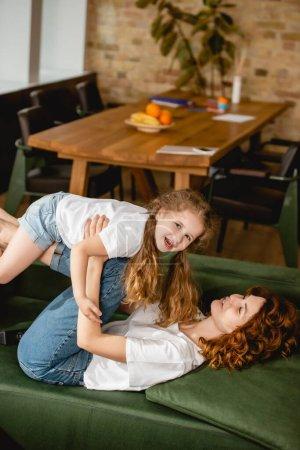 Photo pour La mère couchée sur un canapé, levant sa fille joyeuse et tenant la main dans le salon - image libre de droit