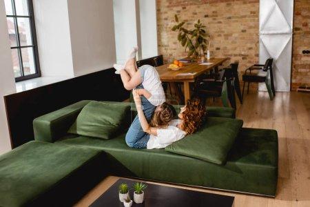 Photo pour Curly mère allongée sur un canapé et levant un mignon enfant dans le salon - image libre de droit