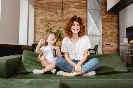 Photo pour Enfant heureux tenant télécommande et assis près de la mère rousse sur le canapé - image libre de droit
