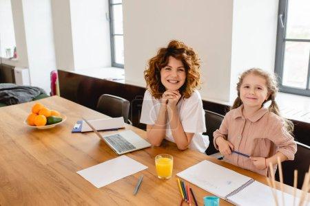 Photo pour Frisé freelance mère souriant près enfant dessin près ordinateur portable - image libre de droit