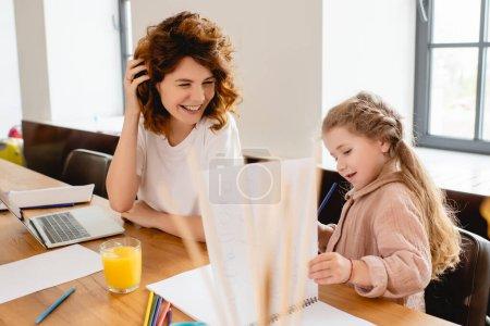 Photo pour Foyer sélectif de la mère bouclée souriant près de l'enfant et de l'ordinateur portable - image libre de droit